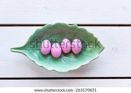 Pink easter eggs in a plated shaped as al leaf one vintage wooden background - stock photo