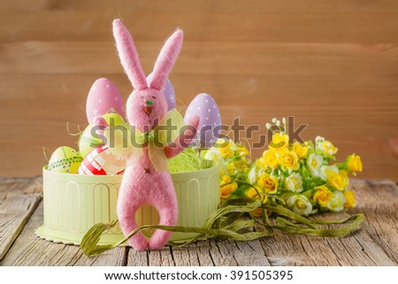 Pink easter rabbit and eggs in sesal nest
