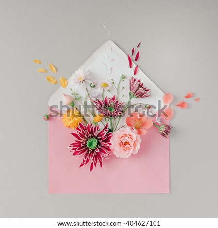Pink envelope full of various flowers. Flat lay. Love concept. - stock photo
