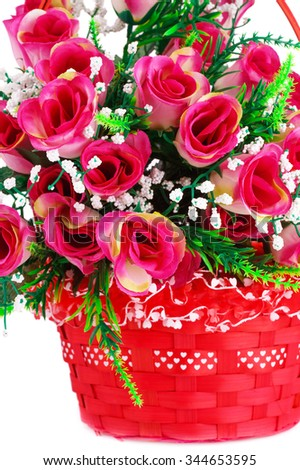 Pink fabric roses in wicker basket isolated on white background. - stock photo