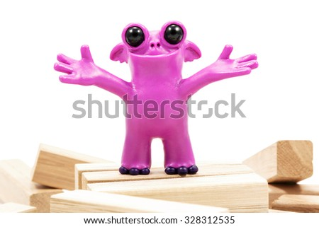 Pink fantastic plasticine monster with a smile on wooden blocks closeup isolated on white background - stock photo