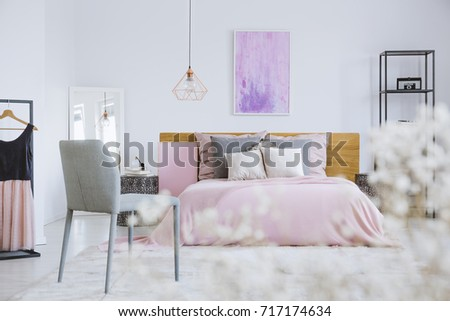 Pink Feminine Bedroom With Watercolor Painting And Simple Gray Chair White Flowers In The Foreground