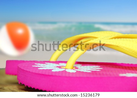 Pink flip flop sandals on dock next to beachball and ocean - stock photo