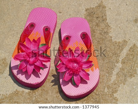 pink flip flop sandals on wet cement surrounding a swimming pool - stock photo