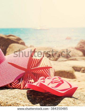 Pink Flip Flops Bag Starfish Accessories Clothes on Stone Beach Coastline Sea Relax Summer Vacation Holiday Concept Toned - stock photo