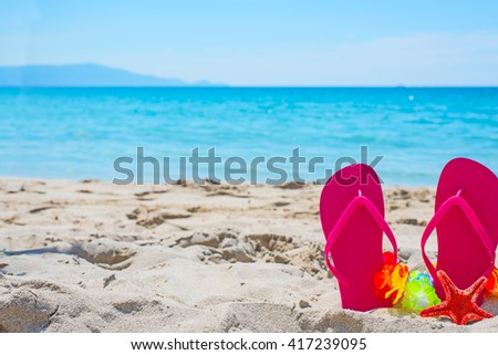 pink flip flops on the sand  - stock photo