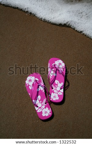 Pink flip-flops on the sand at the beach as a wave approaches - stock photo