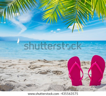pink flip flops under a palm tree by the sea - stock photo