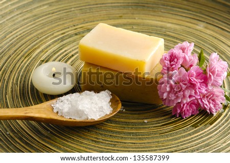 Pink flower and salt in spoon and soap, candle on wooden plate texture