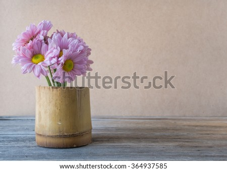 Pink flower in vase made from bamboo on wooden table,