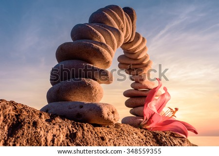 Pink flower of lily near arch of pebbles  - stock photo