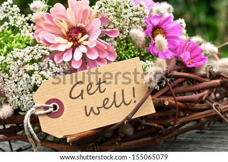pink flowers and card with lettering get well/get well/english - stock photo
