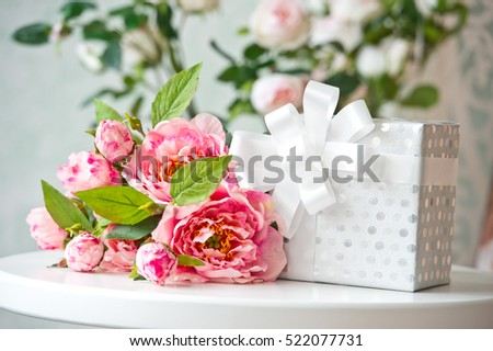 Pink flowers and gift box on the table. Birthday. Interior