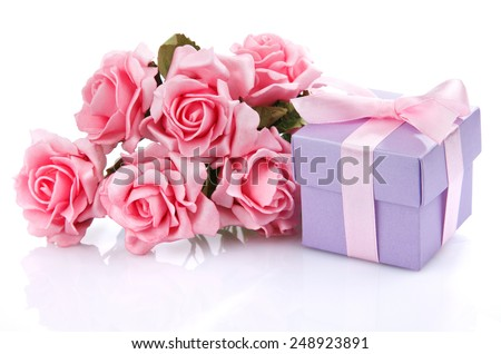 pink flowers and purple gift box with pink ribbon and bow on a white background - stock photo