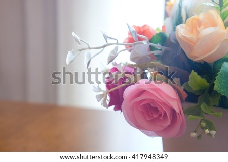Pink flowers in a vase on wood table