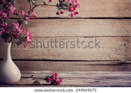 pink flowers in vase on wooden background - stock photo