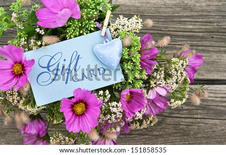 pink flowers with gift card/gift card/flowers - stock photo