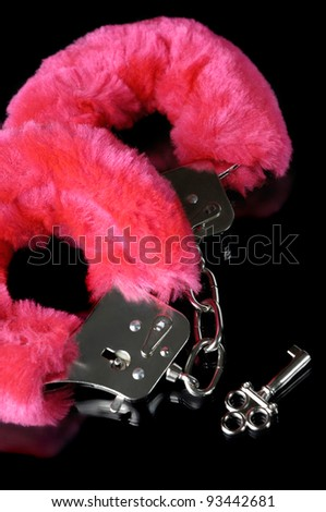 Pink fluffy handcuffs with a key closeup isolated on black background - stock photo