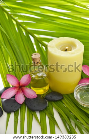 Pink frangipani and yellow candle ,oil ,black stoneson palm leaf - stock photo