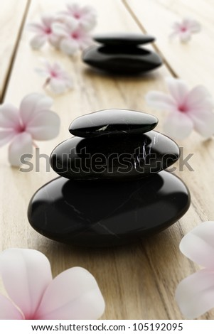 Pink frangipani flower and black stone, zen spa on wood