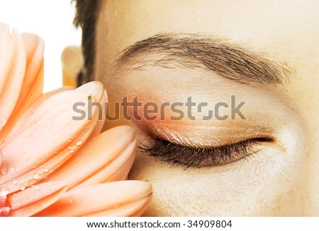 Pink gerber and closed eye of young woman - stock photo