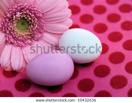 pink gerber and easter eggs on pink and red dotted paper background - stock photo