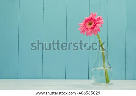 Pink Gerbera daisy flower in bulb glass vase on white and wooden background - stock photo