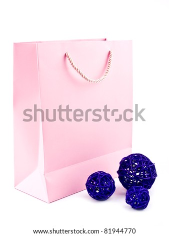 Pink gift bag with purple rattan balls on white background