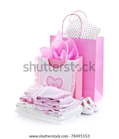Pink gift bags and infant clothes for girl baby shower isolated on white