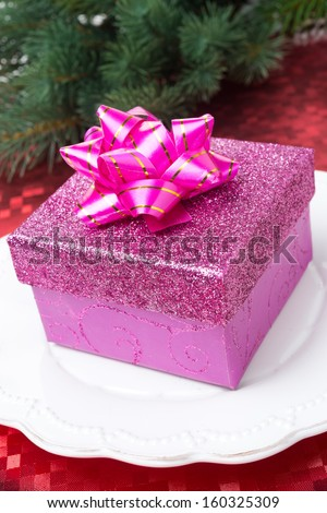 Pink gift box on a plate for Christmas, close-up, vertical - stock photo