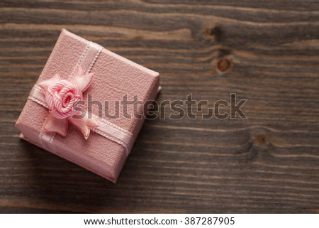 Pink gift box with a bow on a wooden table top view, selective focus, copy space - stock photo