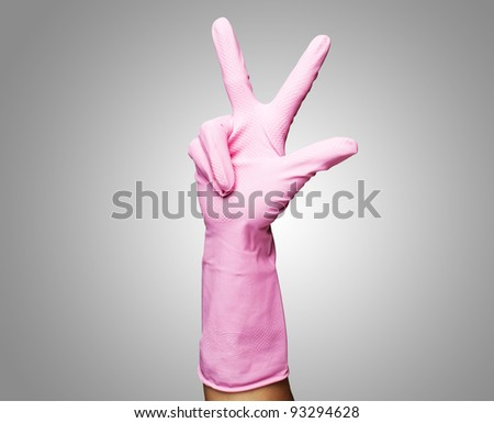 pink glove gesturing the number three against a grey background - stock photo