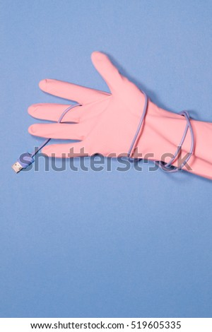 pink glove with cable on blue background