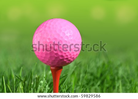 pink golf ball on a tee over green grass outdoors - stock photo