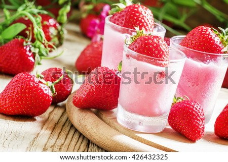Pink granita with strawberries in a glass, old wooden background, selective focus