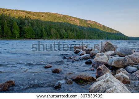 Pink Granite boulders line a part of the shoreline on Jordan Pond in Maine - stock photo