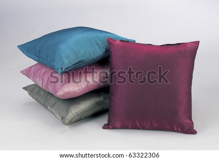 pink, grey, maroon, and blue pillows isolated on plain background. - stock photo