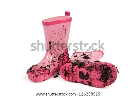 Pink gumboots covered in mud against a white background. Clipping path included. - stock photo