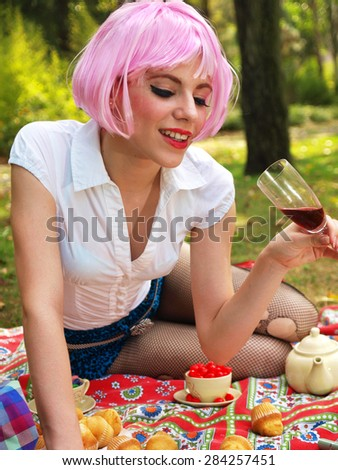 Pink haired pinup girl drinking wine in a picnic - stock photo