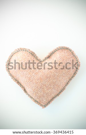 Pink handmade textile fabric heart on white background closeup - stock photo