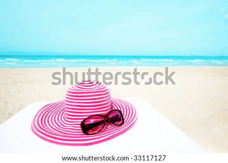 Pink hat and sunglasses near the ocean - stock photo