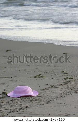 pink hat found at beach - stock photo
