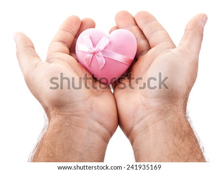Pink heart in male hands on a white background. - stock photo
