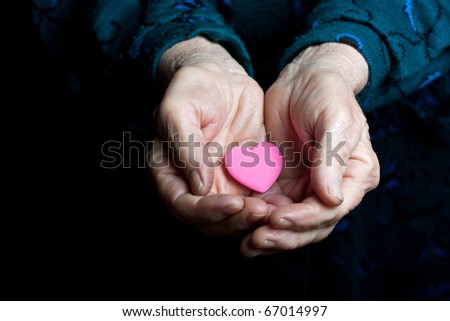 Pink heart in the old hands - stock photo