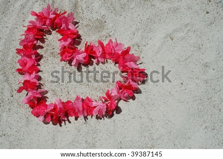 pink heart lei laying on sandy beach room for your text - stock photo