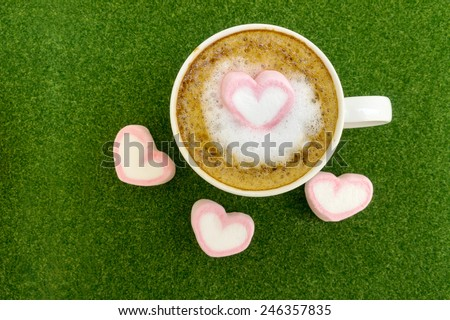 Pink heart marshmallow top on latte milk coffee for valentine's day on green grass background. - stock photo