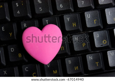 Pink heart on black keyboard - stock photo