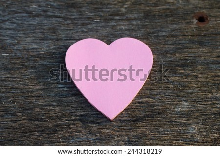 Pink heart post it on rustic wood table - stock photo