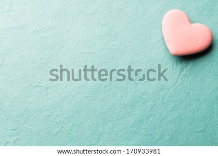 Pink heart-shaped candy on a paper background. - stock photo
