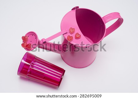 Pink heart-shaped candy on watering can, overturned glass,isolated on a white background, close view.
